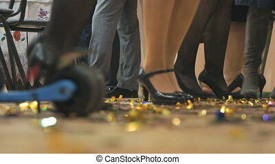 Women and men dancing at a anniversary indoors. Close-up of people's feet
