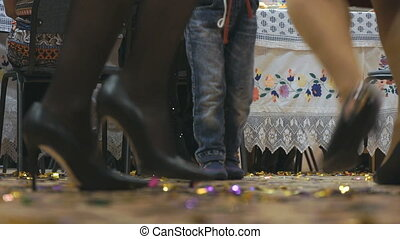 Women's and men feet in moving indoors. Close-up - Women and...