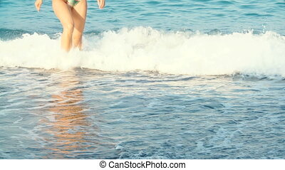women's beautiful tanned legs out of the water at beach....