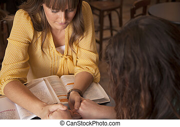 Women's Bible Study - Two women hold hands and pray as they ...