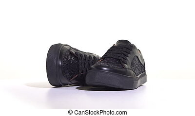 Women's black sneakers on a white background. Rotary table