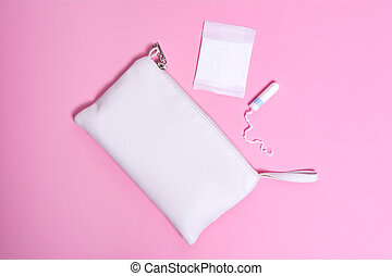 Women's daily panty liner and tampon on a pink background. Intimate hygiene product near white cosmetic bag.