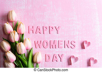 Womens day concept. Pink tulips and paper hearts with Wooden letters forming word Happy Womens day written on pink and white wooden background.