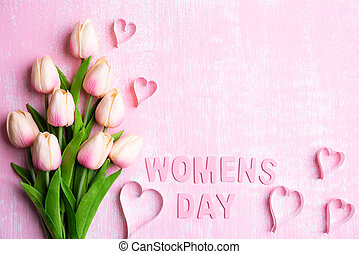 Womens day concept. Pink tulips and paper hearts with Wooden letters forming word Womens day written on pink and white wooden background.