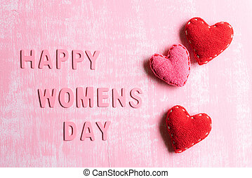 Womens day concept. Red Hearts with Wooden letters forming word Happy Womens day written on pink and white wooden background.