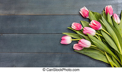 Womens day. Pink tulips bouquet on blue wooden background, copy space, top view
