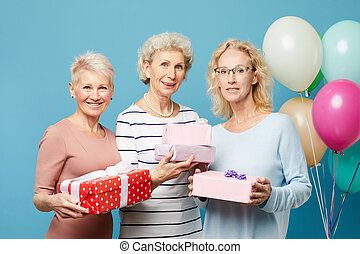 Portrait of smiling beautiful mature ladies standing against heap of balloons and blue wall and holding beautiful gift boxes, womens day concept