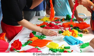 womens do by hands flowers of color paper lying on table