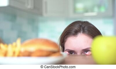 Women's eyes look around choosing between harmful fasfood and a healthy fruit. Dilemma of choice from a young woman between a burger with fried fries and an apple slowmo