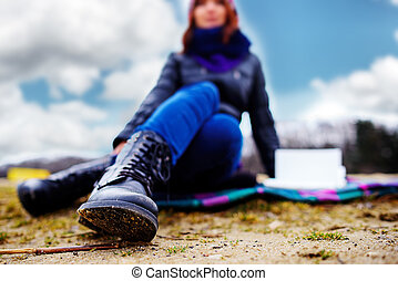 Women's feet in blue jeans and black winter boots are on the san