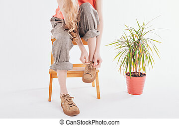 women's feet in linen clothes and shoes next to a flower on a white background