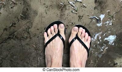 women's feet in slippers in the rain top view
