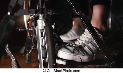 Women's feet in sneakers press the drum pedalswomen's feet...