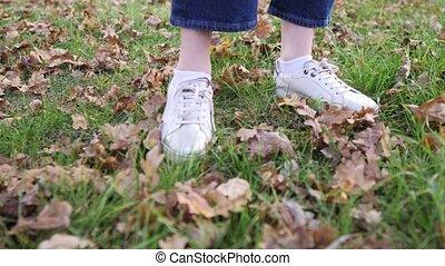 Women's feet in white sneakers on green grass with fallen ...