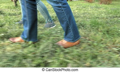 Women's feet on the grass in shoes and sneakers