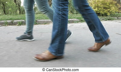 Women's feet on the sidewalk in shoes and sneakers