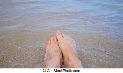 women's feet splashing in sea water on the beach.Closeup