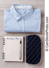 Women's flatlay. Shirt, planner with digits and pen, case. ...