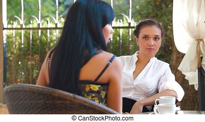 Women's Gossip - Female friends immersed in conversation at...