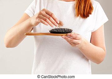 Women's Hair Loss. Beautiful redhair with hair tuft in hair...