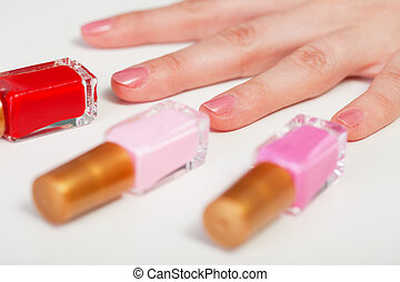 Women's hand and three bottles nail polish