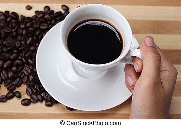 Women's hand holding a coffee cup