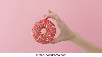 Womens hand holding donut on pink background - Womens hand...