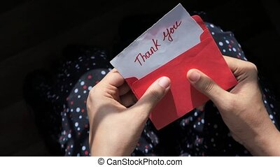 women's hand holding thank you letter , top down .