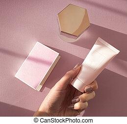 women's hand holds cream