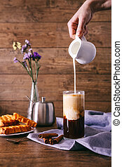 Women's hand with creamer pouring milk in glass with coffee. Cinnamon sticks, homemade cookies and bunch of wildflowers on a wooden background. Breakfast concept.