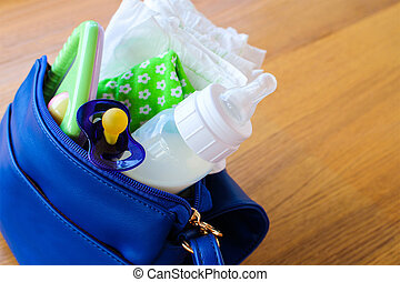 Women's handbag with items to care for child