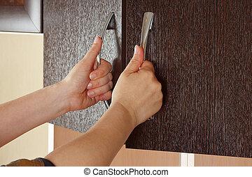 Women's hands are open the cupboard doors, dark wood