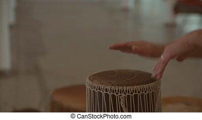 Women's hands beat on bongo musical motifs. Old drum