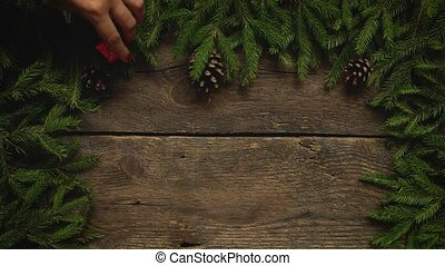 Women's hands create a Christmas decor. Christmas tree branches with cones and christmas decorations on wooden texture ready for your design