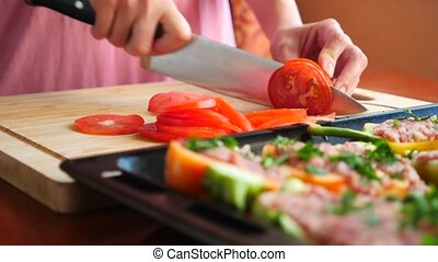 women's hands, cut thin tomato slices into stuffed zucchini....