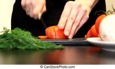 Women's hands cut tomato