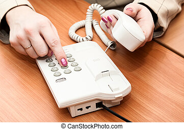 Women's hands dial a telephone number on the white telephone
