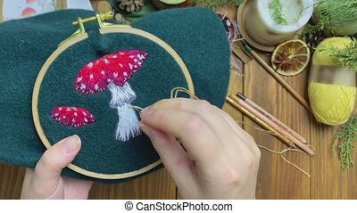 Women's hands embroidery leg of mushroom with floss threads on tambour. Sewing of fly agaric on green beret. Handicrafts workshop. Wooden table with yarn scissors and candle on background.