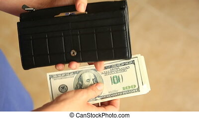 Women's hands hold a money clip with dollars