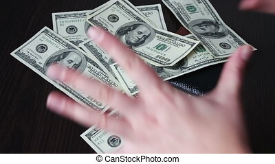 Women's hands holding a fan of hundred dollar bills and counts