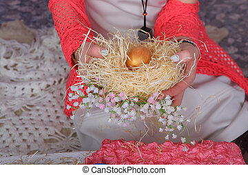 Women's hands holding an egg with nest