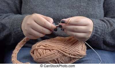 Women's hands knit from grey wool. Hand knitting.