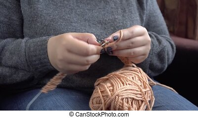 Women's hands knit from grey wool. Hand knitting