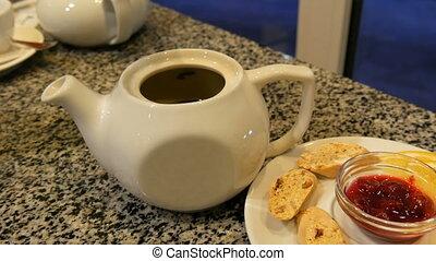 Women's hands lift the lid of the white teapot. Tea set of...