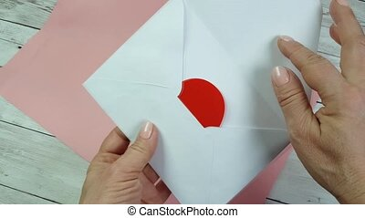 Women's hands open the white envelope and take out a valentine card in the shape of a red heart for the holiday of St. Valentine's Day. Pink background, romantic declaration of love.