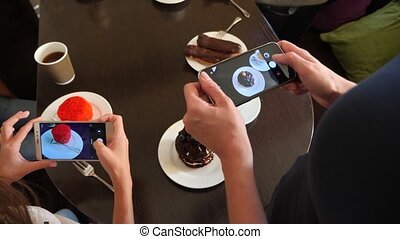 women's hands photography delicious beautiful desserts on their smartphone in a cafe to lay out in social networks. 4k, slow motion shooting