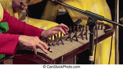 women's hands playing an old musical instrument