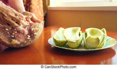 women's hands preparing zucchini stuffed with minced meat...