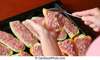 women's hands preparing zucchini stuffed with minced meat...