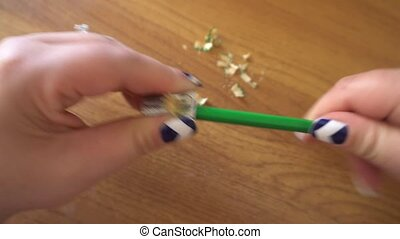 women's hands sharpening pencil sharpener.